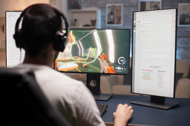 Widok młodego człowieka grającego w gry wideo na komputerze z wieloma monitorami z tyłu.