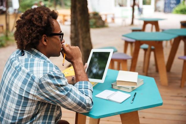 Widok młodego człowieka w okularach, studiowanie i używanie tabletu w kawiarni na świeżym powietrzu z tyłu