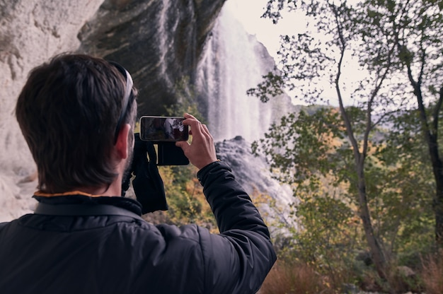 Widok młodego człowieka z tyłu robiącego zdjęcie siklawy z tyłu swojego smartfona.