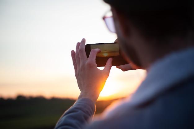 Widok młodego faceta z tyłu robić zdjęcia zachodu słońca smartfonem