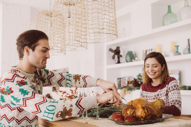 Widok młodego mężczyzny i kobiety siedzą na świątecznym stole gotowi do spożycia pieczonego indyka