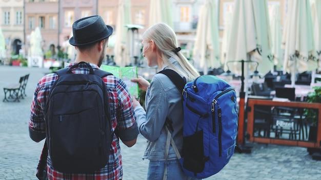 Widok młodego mężczyzny i kobiety z torby sprawdzanie mapy na centralnym placu miasta z tyłu. dyskutują o swoim nowym miejscu docelowym.