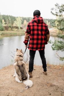 Widok młodego mężczyzny w casual, trzymając smycz swojego zwierzaka z tyłu, jednocześnie patrząc na jezioro podczas chłodu w parku lub lesie