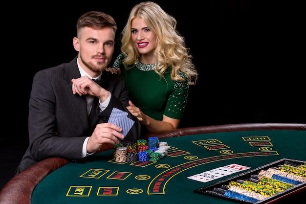 Widok młodego, pewnego siebie mężczyzny z panią podczas gry w pokera. oboje patrzą w kamerę i uśmiechają się