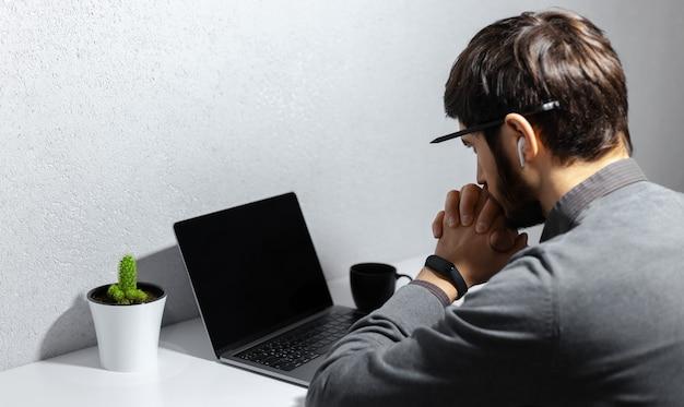 Widok młodego, przemyślanego biznesmena z ołówkiem na uchu, patrząc w laptopa, używając bezprzewodowych słuchawek, noszącego smartwatch, filiżankę kawy i kaktusa na białym biurku z tyłu.