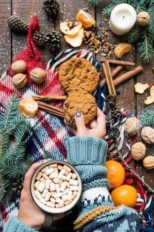 Widok młodej dłoni kobiet biorąc plik cookie podczas gorącej kawy z piankami na zimowy wieczór