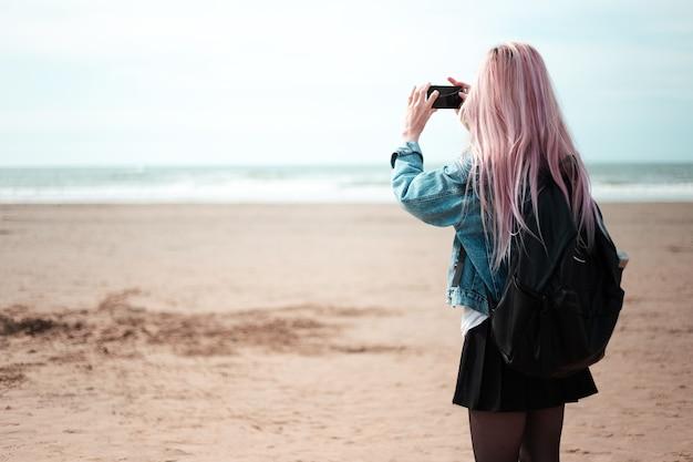 Widok młodej dziewczyny z różowymi włosami i czarnym plecakiem z tyłu, podziwiając morze ze smartfonem w dłoni.