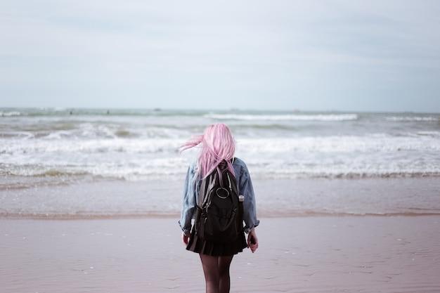 Widok młodej dziewczyny z różowymi włosami i czarnym plecakiem z tyłu, podziwiając morze.