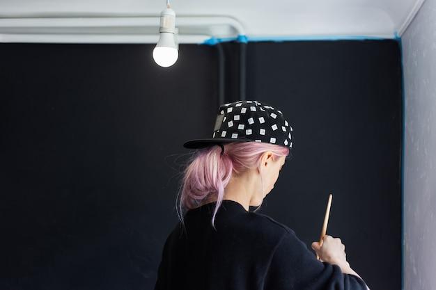 Widok Młodej Dziewczyny Z Różowymi Włosami, Malowanie ścian Pędzlem I Białym Kolorem Z Tyłu, Odświeżenie Mieszkania. Nosi Czarną Czapkę I Sweter. Premium Zdjęcia