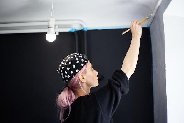 Widok młodej dziewczyny z różowymi włosami, malowanie ścian pędzlem i białym kolorem z tyłu.