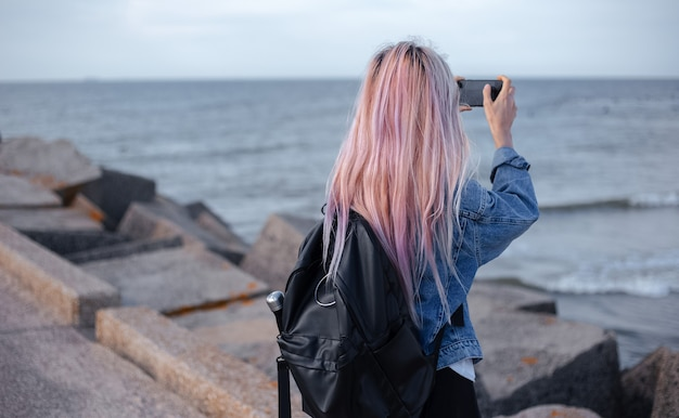 Widok młodej dziewczyny z różowymi włosami, ubrana w dżinsową kurtkę i czarny plecak z tyłu