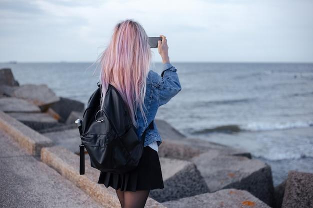 Widok Młodej Dziewczyny Z Różowymi Włosami, Ubrana W Dżinsową Kurtkę I Czarny Plecak Z Tyłu Premium Zdjęcia
