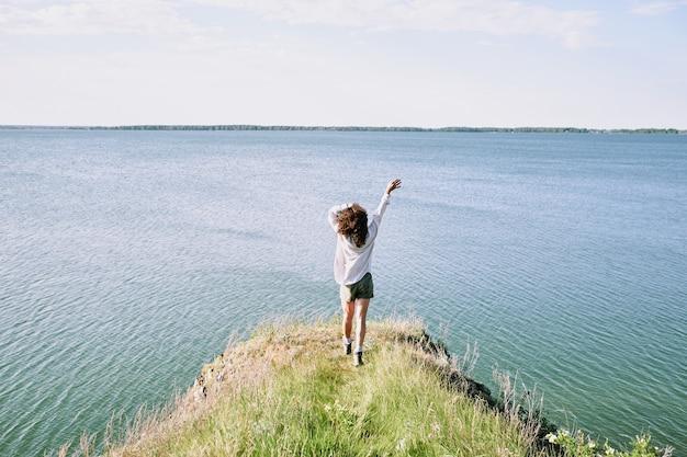 Widok młodej ekstatycznej kobiety o ciemnych, kręconych włosach z tyłu, cieszącej się wolnością i słonecznym dniem, poruszając się w kierunku wody z podniesionymi rękami