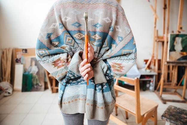 Widok młodej kobiety artysty w swetrze stojącej i trzymającej pędzel w warsztacie z tyłu