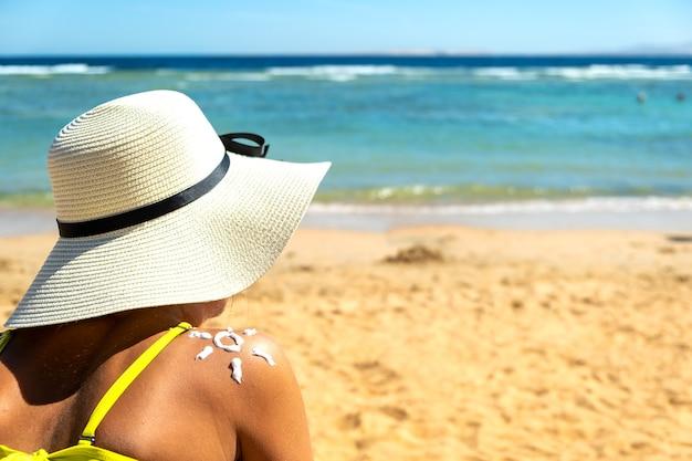 Widok młodej kobiety opalającej się na plaży z kremem przeciwsłonecznym z tyłu