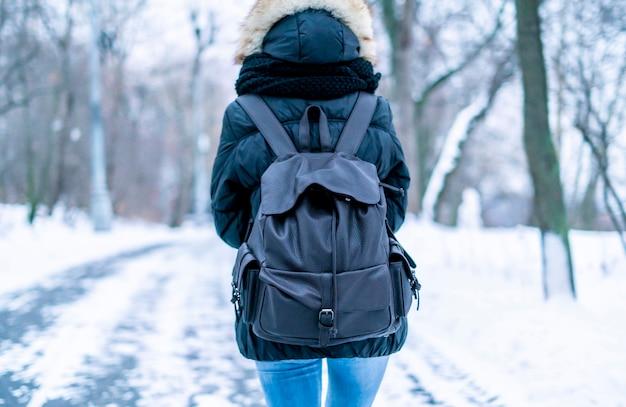 Widok młodej kobiety spaceru w niesamowitym winterorest z tyłu z ogromnym plecakiem
