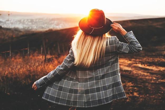 Widok młodej kobiety w stylowym kapeluszu i kurtce stojącej w pięknej okolicy podczas cudownego zachodu słońca z tyłu. nie do poznania elegancka dama na wsi podczas zachodu słońca