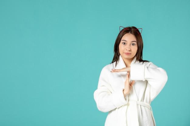 Widok młodej kobiety w szlafroku na niebieskiej ścianie z przodu