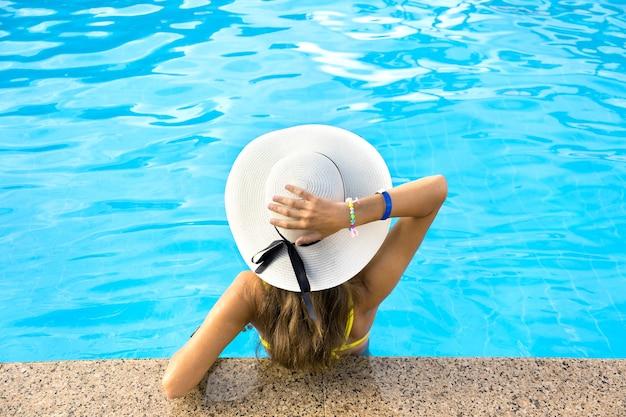 Widok młodej kobiety z długimi włosami na sobie żółty słomkowy kapelusz z tyłu relaks w ciepłym letnim basenie z błękitną wodą w słoneczny dzień