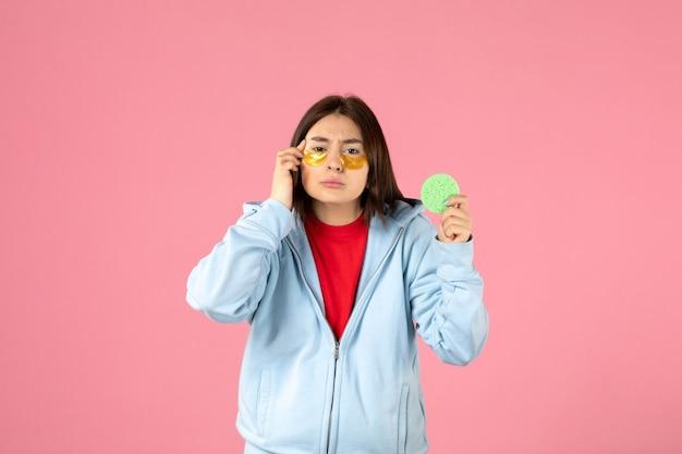 Widok młodej kobiety z opaskami na oczy i małą gąbką na różowej ścianie z przodu