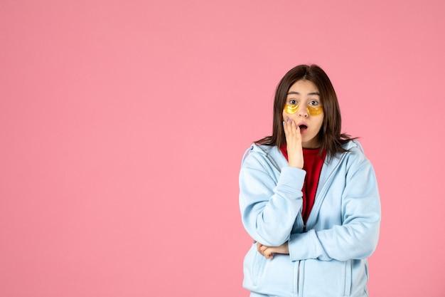 Widok młodej kobiety z opaskami na oczy na różowej ścianie z przodu