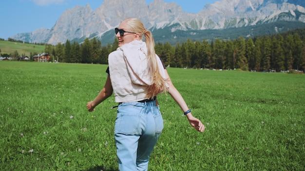 Widok młodej kobiety z tyłu na polu z górami z przodu
