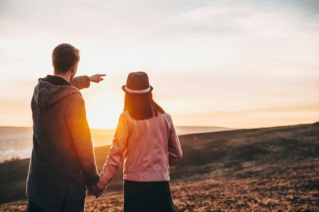 Widok młodej pary podróżującej po świecie z tyłu, podczas gdy mężczyzna pokazuje palcem swojej dziewczynie, gdzie oglądać przed zachodem słońca.