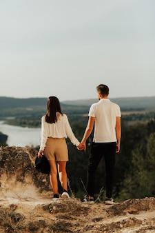 Widok młodej pary stylowe trzymając się za ręce z przyrodą z tyłu.