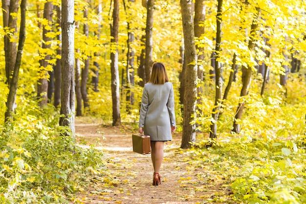 Widok młodej stylowej kobiety z retro walizką spaceru w parku jesień z tyłu