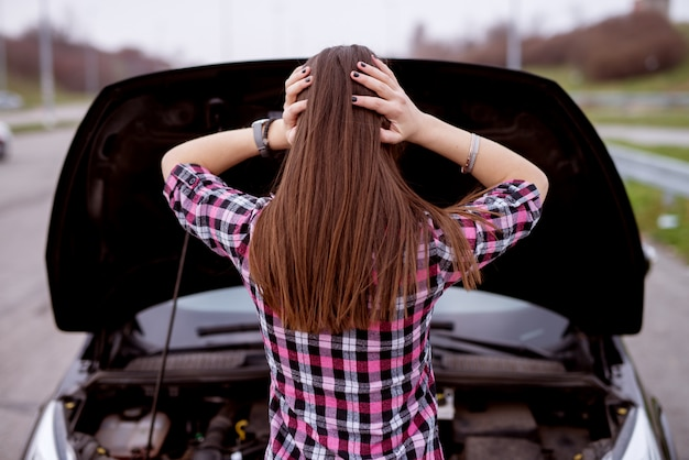 Widok młodej zestresowanej pięknej dziewczyny z tyłu patrzy pod maskę swojego samochodu i trzyma głowę w rozpaczy.