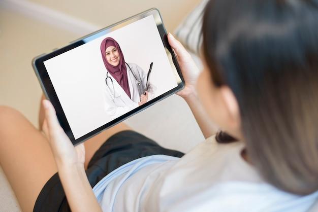 Widok monitora tabletu przez ramię dziewczyny, muzułmańska kobieta lekarz ma na sobie mundur i udziela konsultacji młodym kobietom, koncepcja technologii opieki zdrowotnej