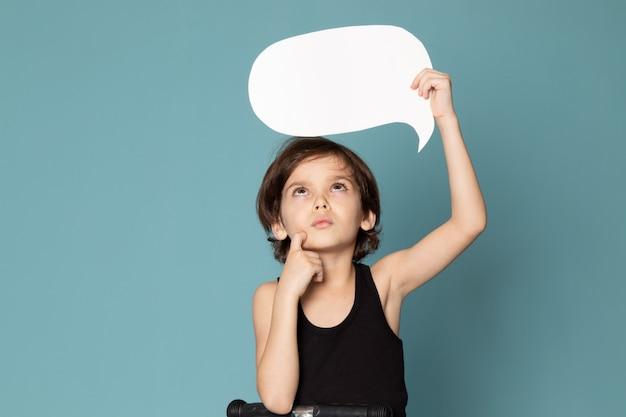 Widok myślącego chłopca, słodkiego, uroczego, uroczego, trzymającego biały znak w czarnej koszulce na niebieskiej przestrzeni