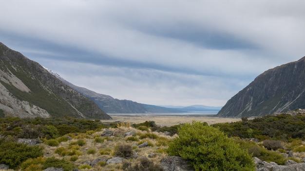 Widok na alpejską dolinę z pochmurnym niebem nakręcony w parku narodowym aoraki mt cook w nowej zelandii