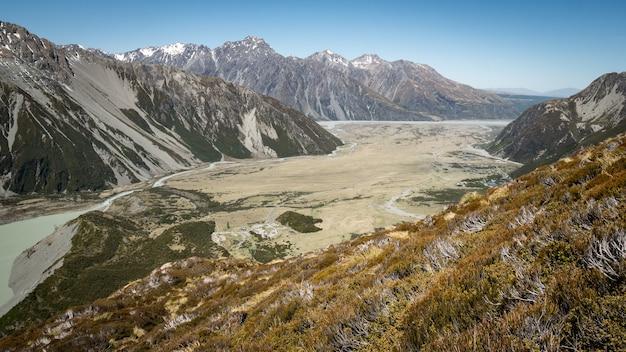 Widok na alpejską dolinę z suchymi kępami na pierwszym planie nakręcony w nowej zelandii