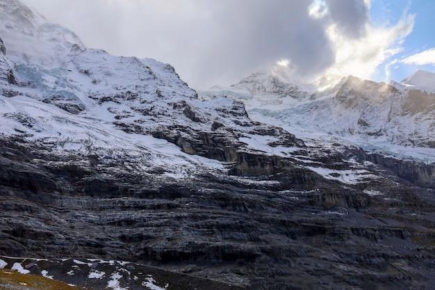 Widok na alpejskie góry jesienią ma śnieg na szczycie wzgórza