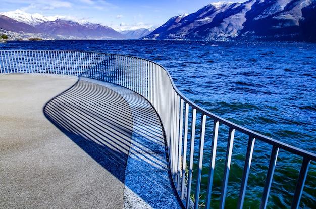 Widok na alpejskie jezioro maggiore z ośnieżoną górą w ticino w szwajcarii