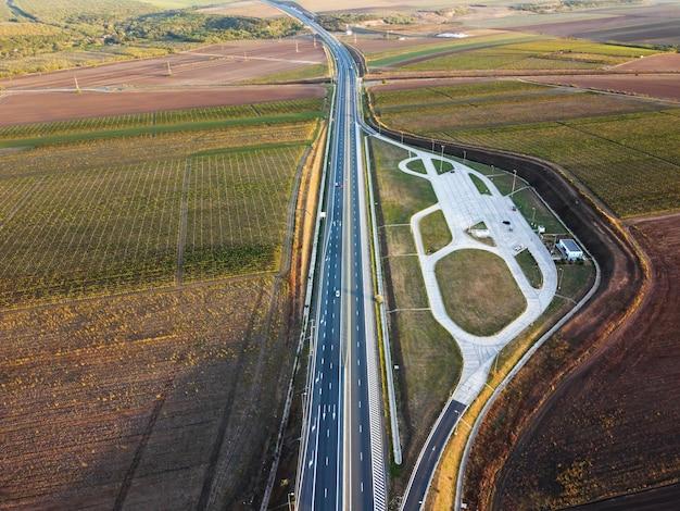 Widok na autostradę z samochodami z drona, parking, pola leśne w rumunii