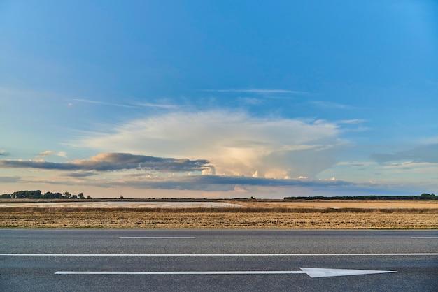 Widok na autostradę ze strzałką w przód i zachód słońca w polu.