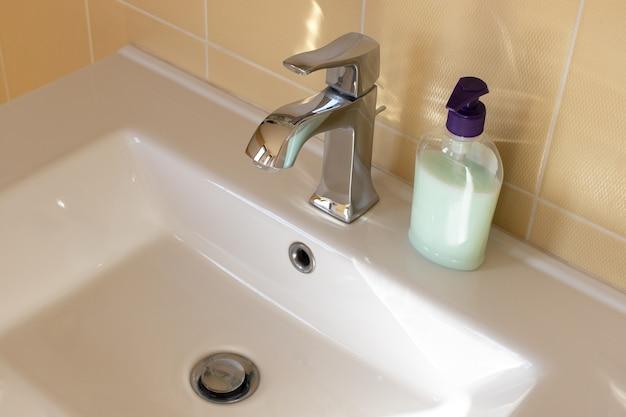 Widok na białą umywalkę łazienkową ze współczesną baterią, nieopisaną butelką mydła w płynie. koncepcja nowoczesnego wnętrza, oszczędność wody, higiena codzienna. widok z boku, zbliżenie. format poziomy.