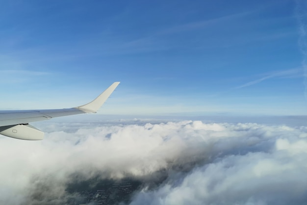 Widok na białe puszyste chmury na niebieskim niebie pod skrzydłem samolotu