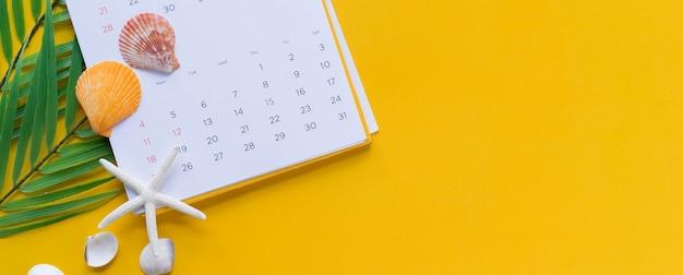 Widok na biały kalendarz z ołówkiem i tropikalnymi liśćmi i muszlami na żółtym tle
