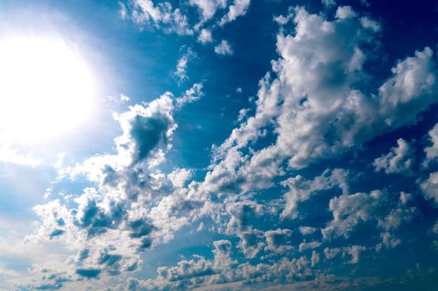 Widok na błękitne niebo i duże białe chmury w promieniach słońca. tło nieba. panorama nieba z białymi i ciemnymi chmurami