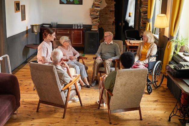 Widok na całą długość grupy starszych osób siedzących w kręgu podczas sesji terapeutycznej w domu spokojnej starości, skupienie się na płaczu kobiety, kopiowanie miejsca