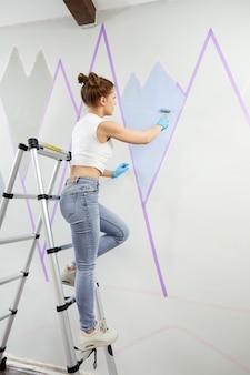 Widok na całą długość młodej kobiety malującej ścianę wałkiem do malowania i używając taśmy maskującej podczas