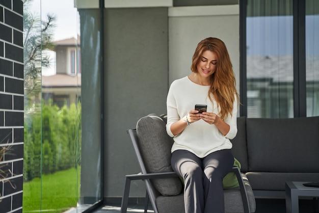 Widok na całą długość uśmiechniętej rudej pani siedzącej na przytulnym tarasie swojej willi. kobieta trzymająca smartfona i uśmiechająca się do ekranu