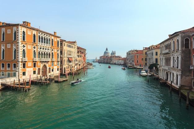 Widok na canal grande. różne łodzie pływają obok pięknego architektonicznego kompleksu nasypów