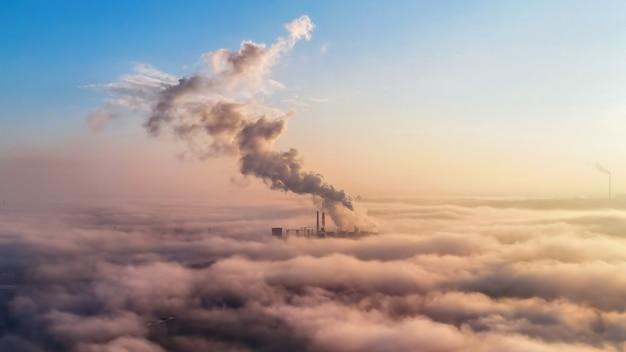 Widok na ciepłownię w oddali ponad chmurami, słupy dymu, idea ekologii
