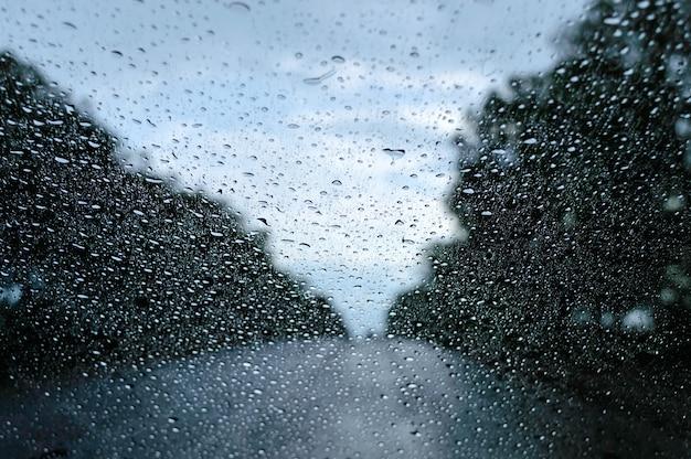 Widok na deszczową pogodę przez przednią szybę samochodu jadącego wzdłuż drogi.