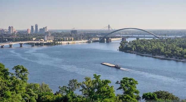 Widok na dniepr i miasto kijów na ukrainie, z mostu dla pieszych w słoneczny letni poranek