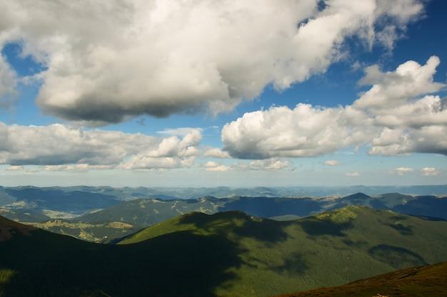 Widok na dolinę ze szczytu góry na tle kilku zalesionych gór i nieba z chmurami